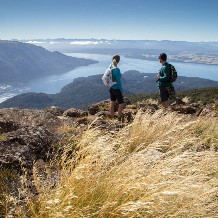 Overlook Lake Te Anau and the expansive landscape below as you hike along the Kepler Track