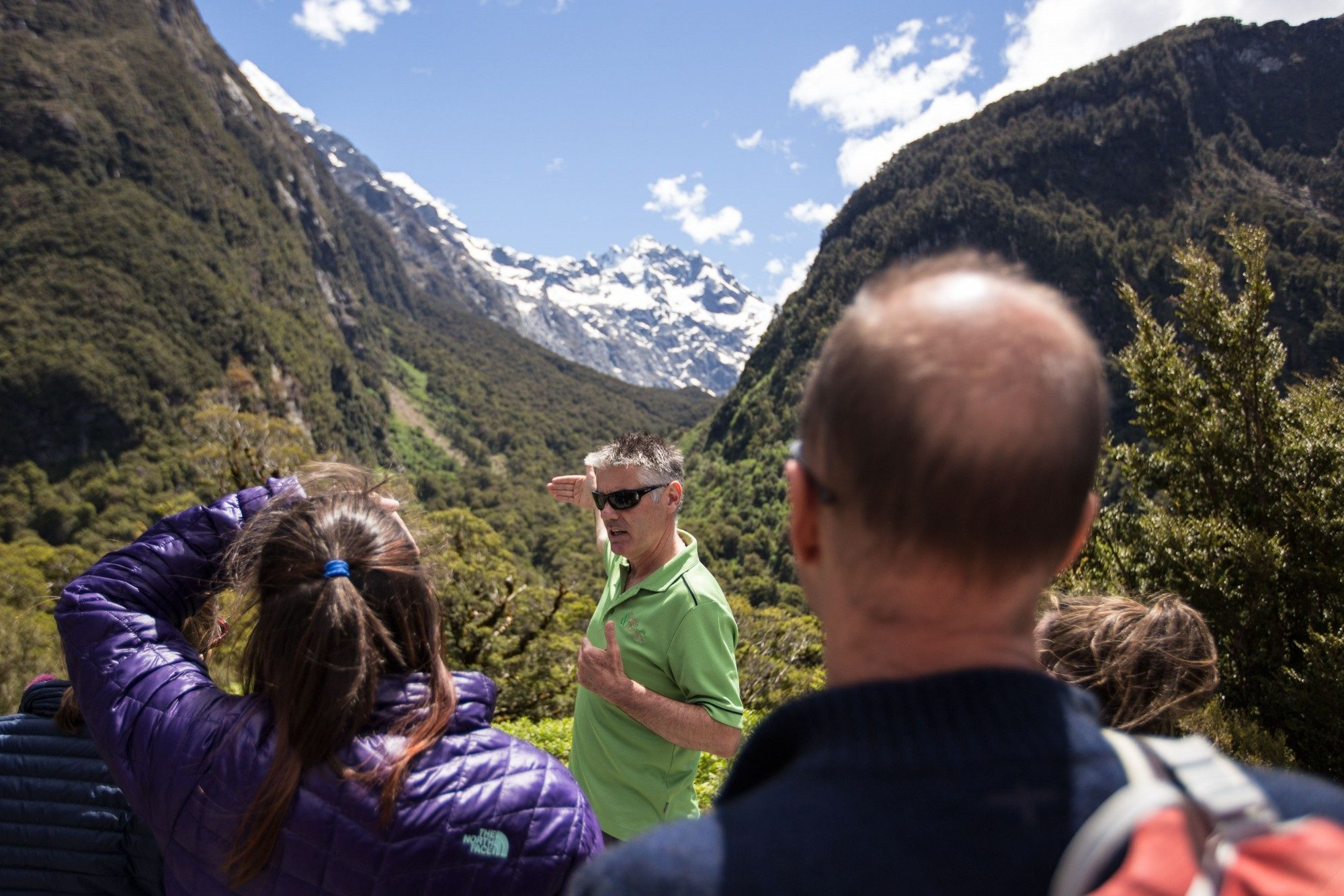 Guide infront of people showing the alpine area.