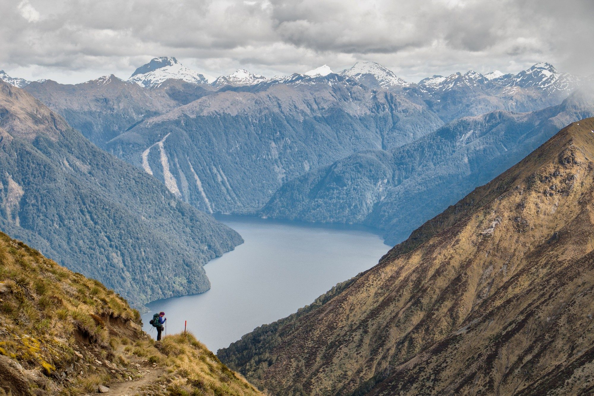 Person tramping in mountains above large lake