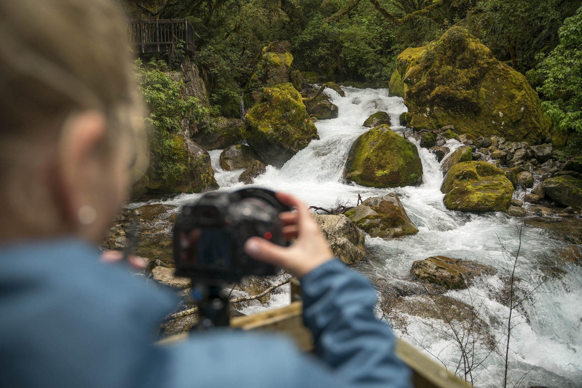 Person taking photo of waterfall