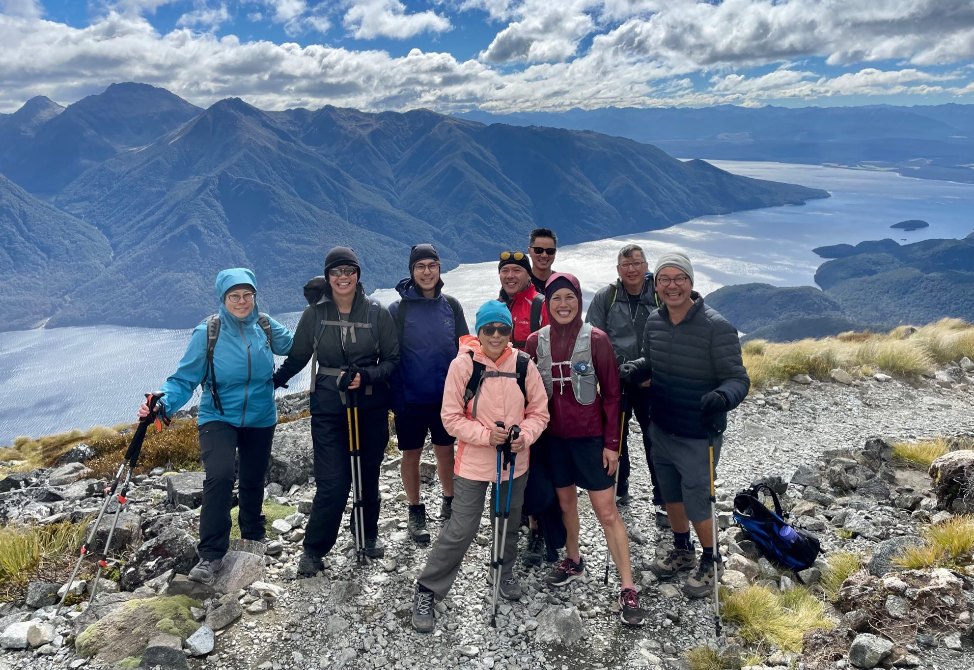 Group of trampers on mountain track above lake