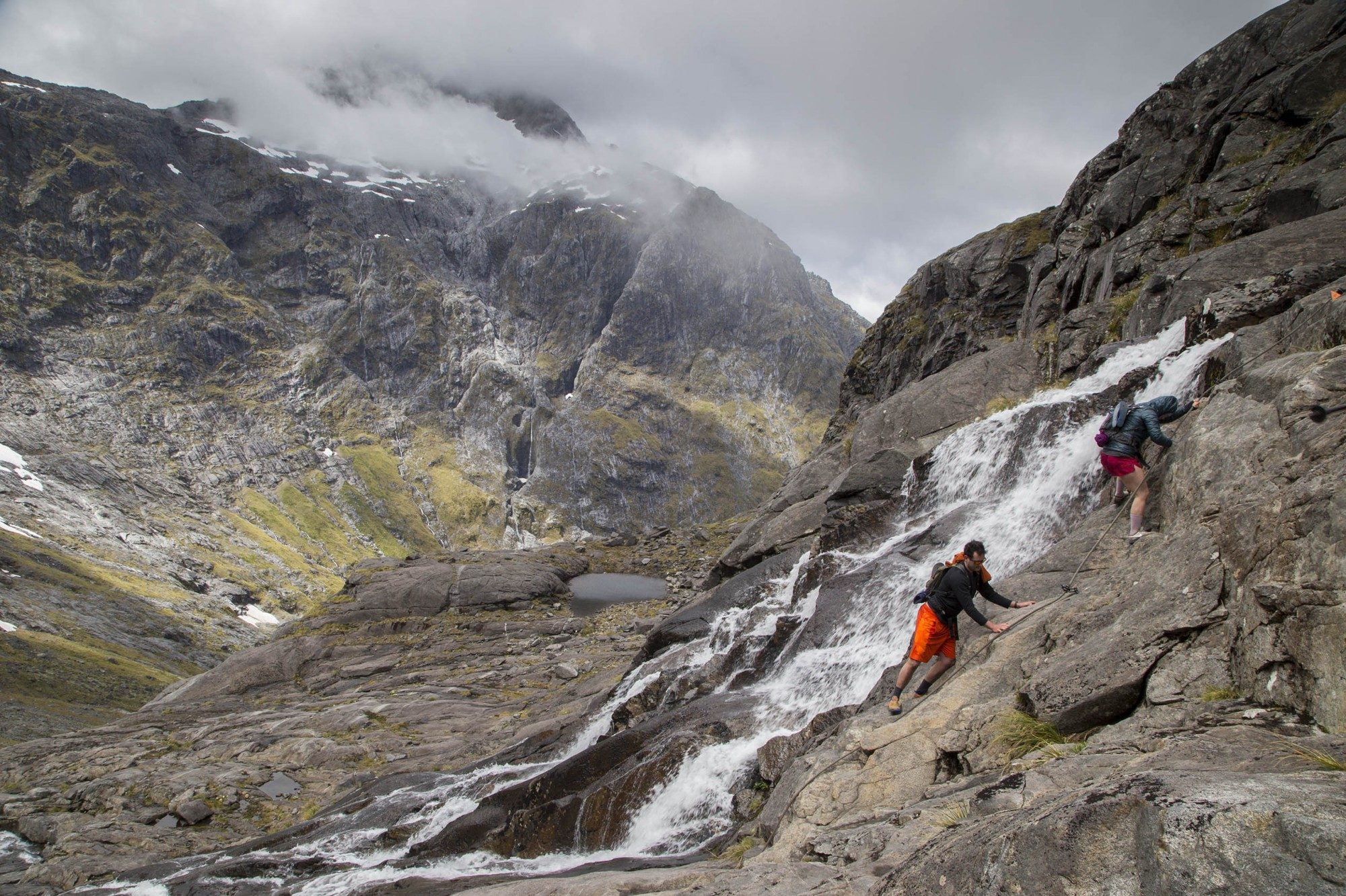 People climbing up the mountain with a waterfall behind them