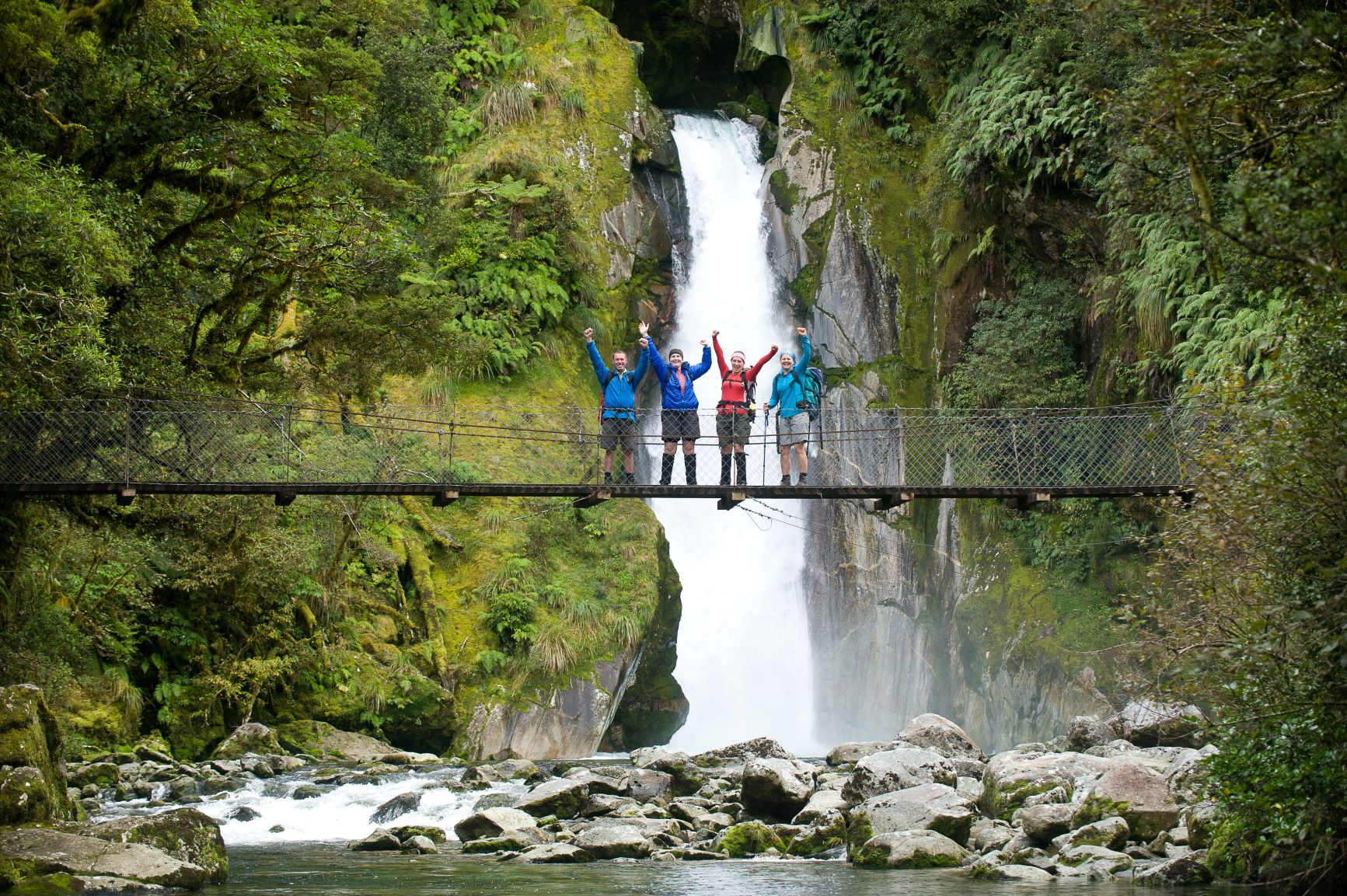 Group of people on swing bridge with water fall behind