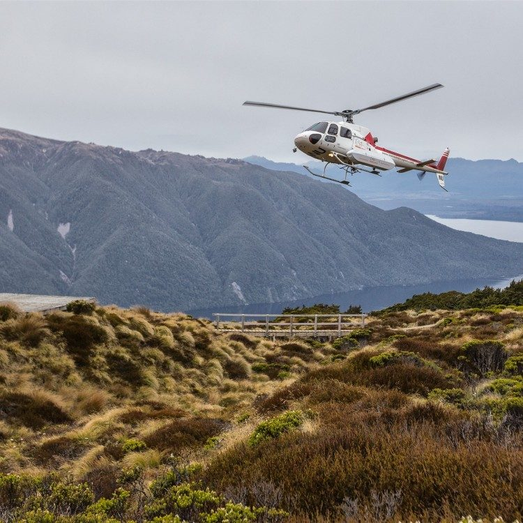 Helicopter coming into land at Luxmore Hut